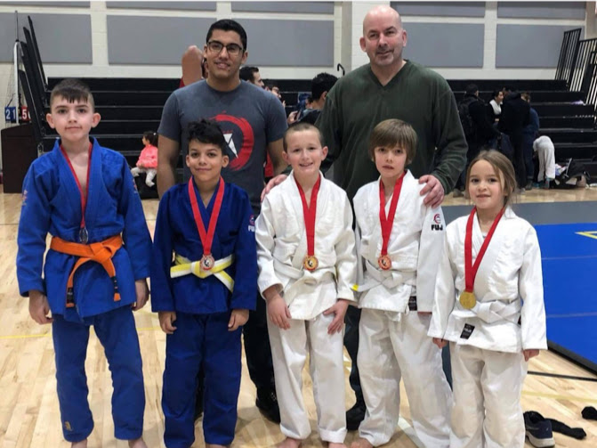 Kids showing off their medals at a judo competition