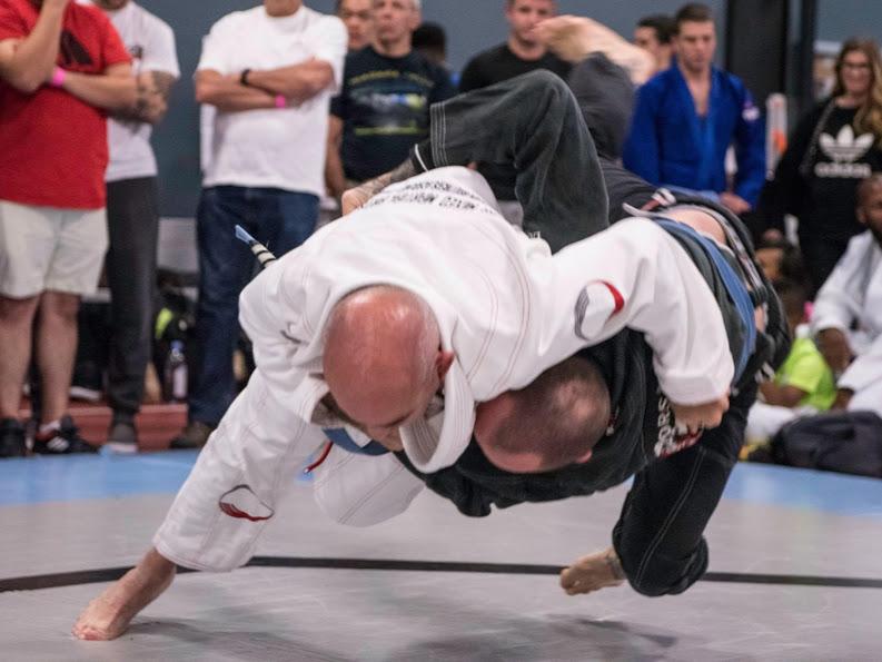 Judoka executing an uchi mata during a BJJ competition